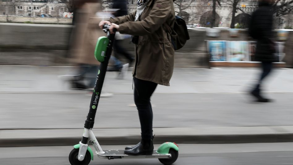 Eine Frau auf einem E-Scooter in Paris