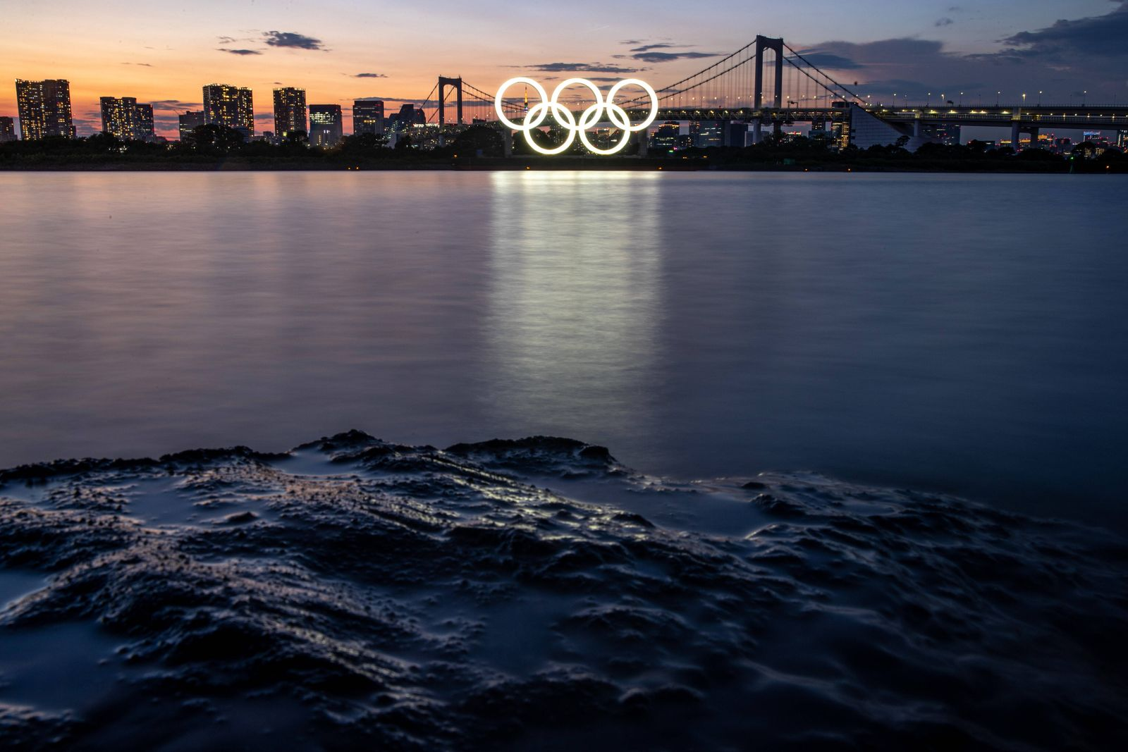 TOKYO, JAPAN - JULY 22, 2021: A barge carrying the Olympic Rings passes Rainbow Bridge over Tokyo Bay. Tokyo was to host