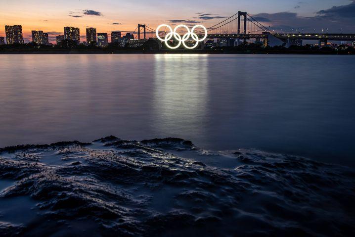 Eine Barke trägt die olympischen Ringe durch die Bucht von Tokio