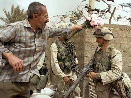 Ein Iraker schmückt einen US-Soldaten mit Blumen