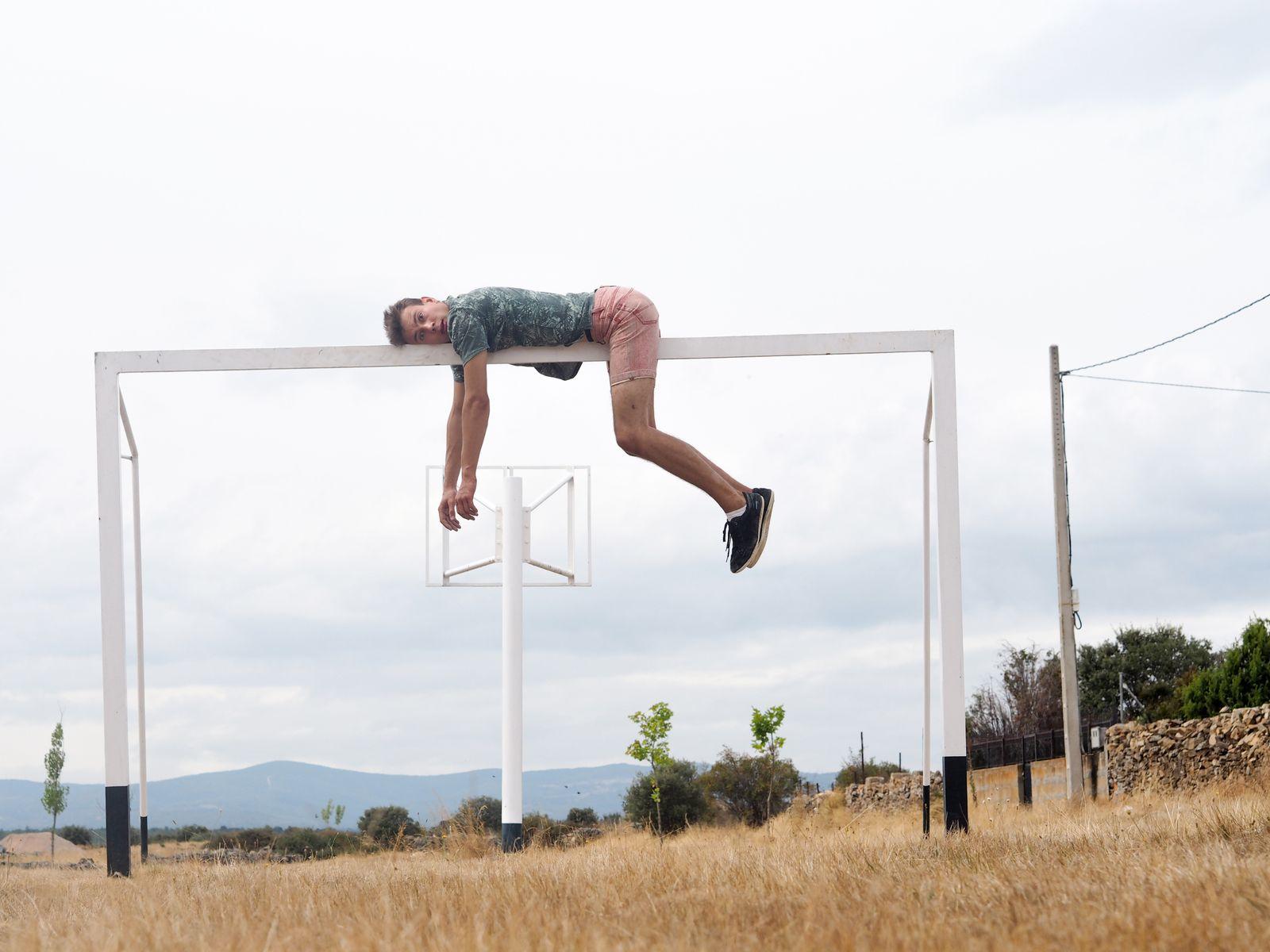 Full Length Of Man Lying On Soccer Goal Post Against Sky