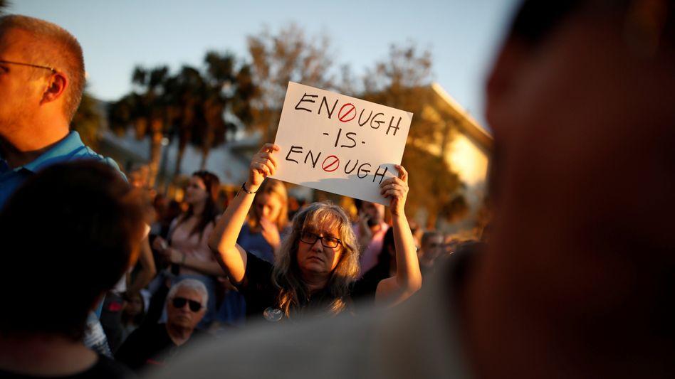 """Eine Frau trägt ein Schild mit der Aufschrift """"Genug ist genug"""""""