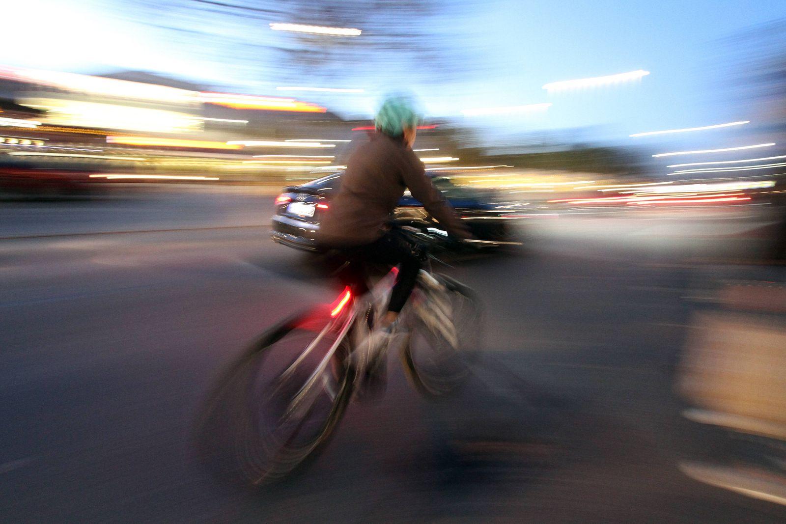 Radfahrer radelt auf einer Straße in der Innenstadt von Heidelberg und wird von einem Auto überholt, Baden Württemberg,