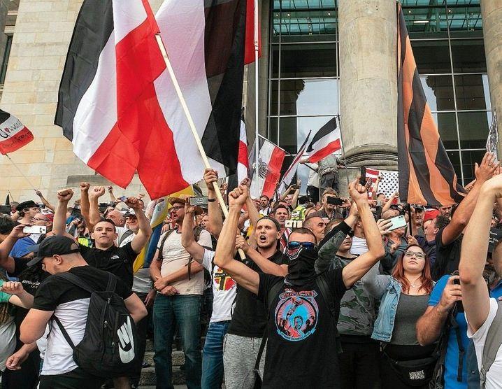 An den Demonstrationen gegen die Corona-Auflagen vor dem Reichstagsgebäude in Berlin nahmen auch rechtsextremistische Personen teil. Die schwarz-weiß-rote Flagge ist ein Symbol, das oft von Neonazis benutzt wird. Auf dem schwarzen T-Shirt des Mannes vorn steht, dass er einen bekannten Rechtsextremisten unterstützt.