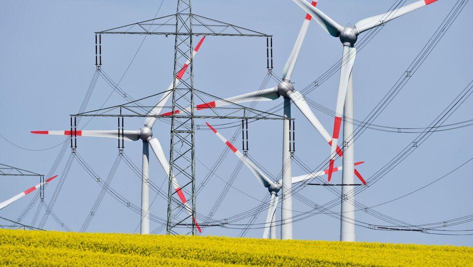 Windräder neben einer Hochspannungsleitung: Hohe Kosten für Energiewende