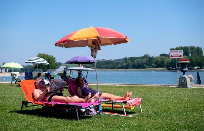 Ein Ehepaar genießt das heiße Wetter am Waginger See in Bayern
