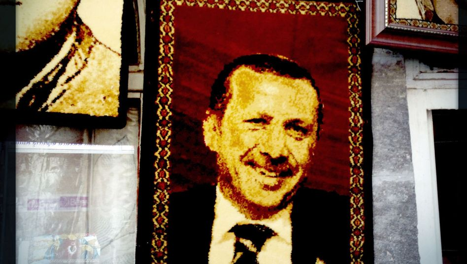 An embroidered image of Turkish Prime Minister Recep Tayyip Erdogan hangs outside a rug shop.