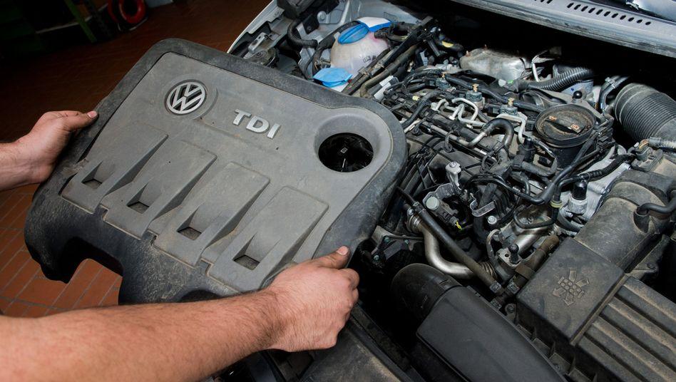 Ein Techniker mit der Abdeckung eines VW-Dieselmotors