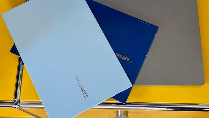 Die drei getesteten Notebooks in zwei unterschiedlich beleuchteten Umgebungen: Das Galaxy Book Ion (oben auf dem Stapel) zeigt passend zur Umgebung changierende Farben