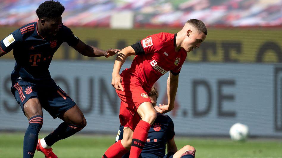 Leverkusens Florian Wirtz (rechts) im Zweikampf mit Bayerns Alphonso Davies