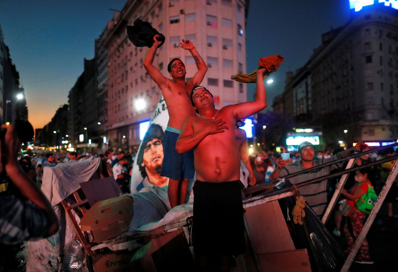 Garbage collectors mourn the death of Argentine soccer great Diego Maradona, at the Obelisk of Buenos Aires, Argentina