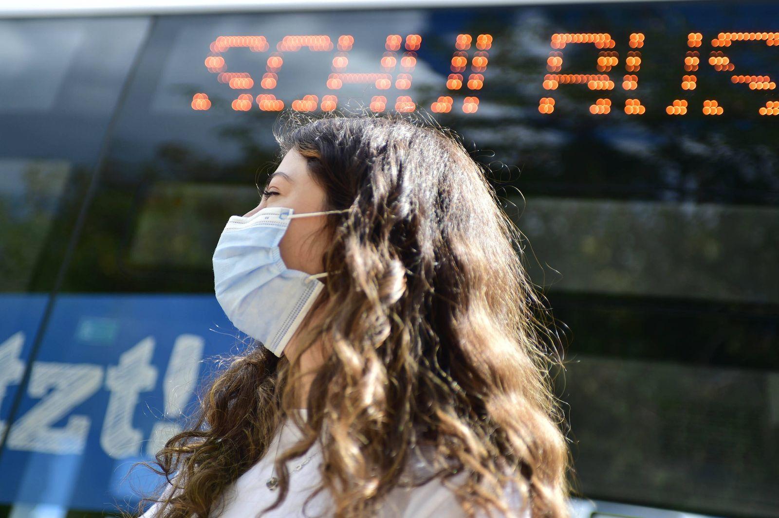 Eine Schülerin wartet an der Gemeinschaftsschule Bellevue in Saarbrücken auf den Schulbus und trägt für die Fahrt einen