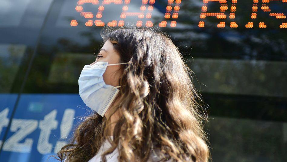 Eine Schülerin wartet auf einen Bus (Archivbild)