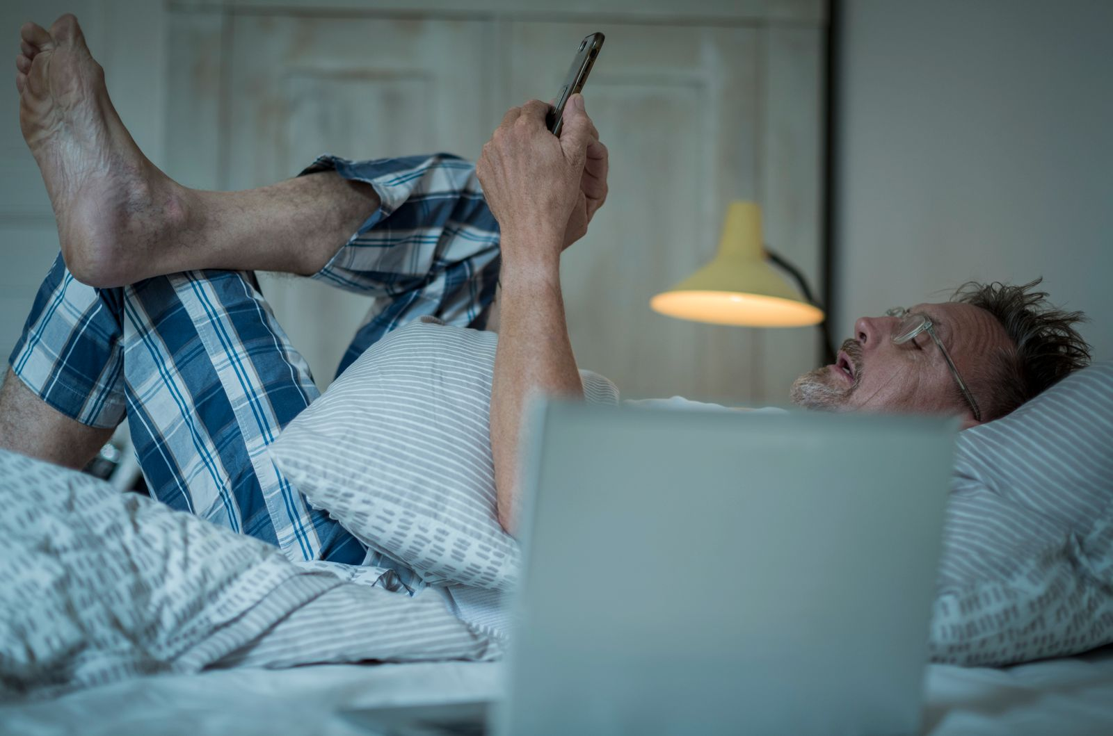 Unhealthy senior man in his 60s with greying beard sleepless in bed while night using laptop and smart phone.