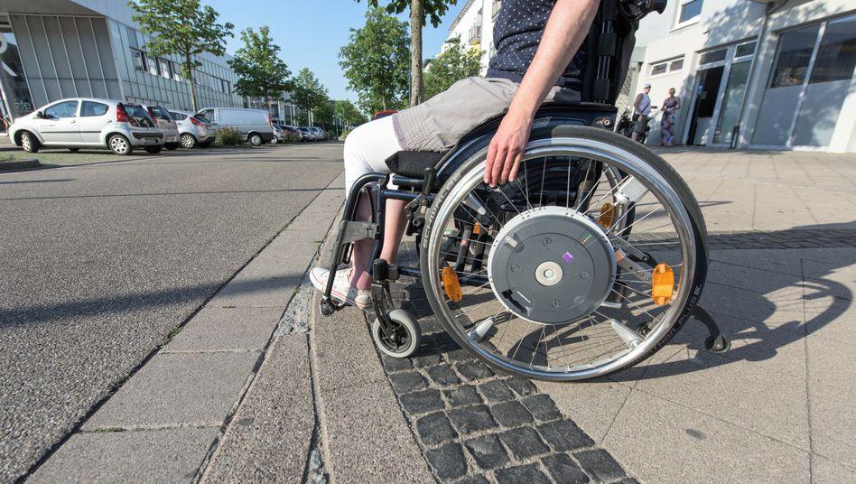 Rollstuhlfahrerin an einem abgesenkten Bordstein in Freiburg