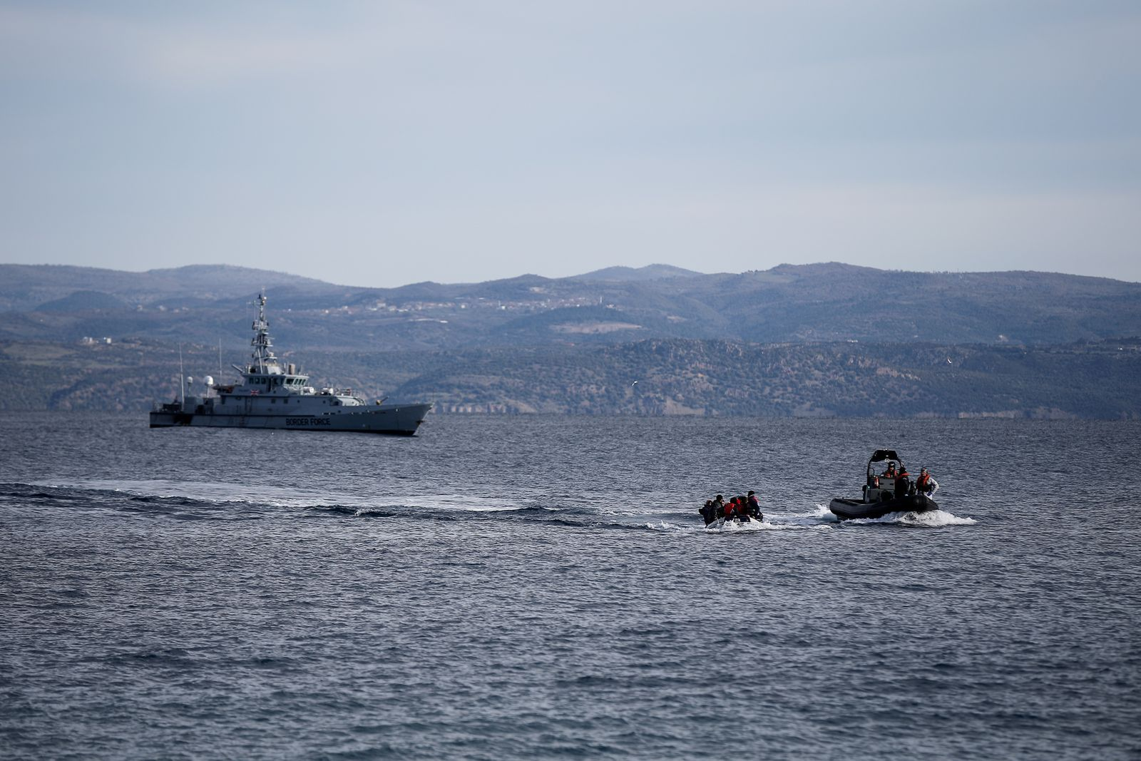 A rescue boat escorts a dinghy with migrants from Afghanistan as a Frontex vessel patrols in the background, on the island of Lesbos