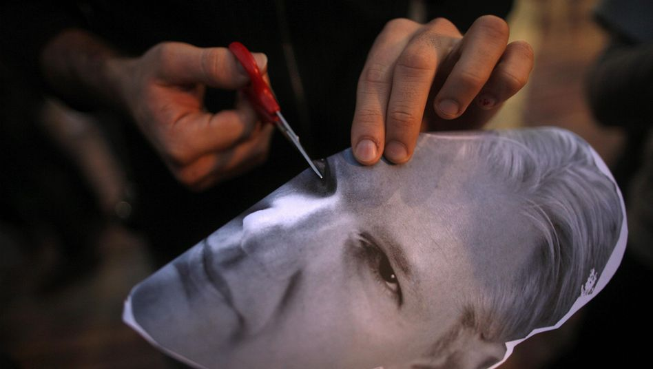 A protester prepares a Julian Assange mask at a pro-WikiLeaks demonstration in Malaga, Spain, on Saturday.