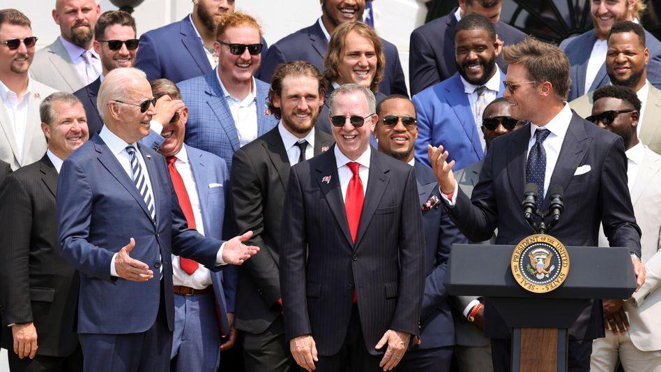 Tom Brady (am Pult) bei seiner Rede im Weißen Haus, neben ihm stehen der Besitzer der Tampa Bay Buccaneers, Bryan Glazer, und US-Präsident Joe Biden
