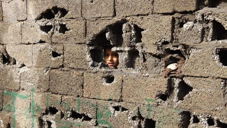 A boy peers through a hole in a damaged wall along a street in the city of Sirnak, near Cizre, southeastern Turkey.
