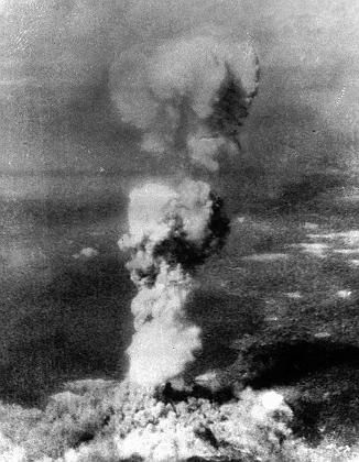 "A column of smoke rises 20,000 feet over Hiroshima, Japan after ""Little Boy,"" the first atomic five-ton bomb, was dropped."