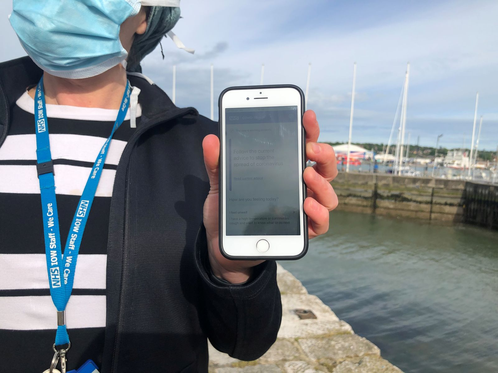 UK National Health Service employee Anni Adams shows a smartphone displaying the new NHS app to trace contacts with people potentially infected with the coronavirus disease (COVID-19) being trialled on Isle of Wight