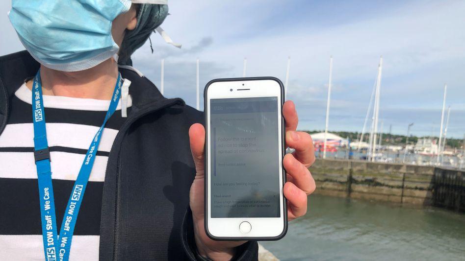 Eine Mitarbeiterin des britischen Gesundheitsdienstes führt die neue NHS-App auf ihrem Handy vor