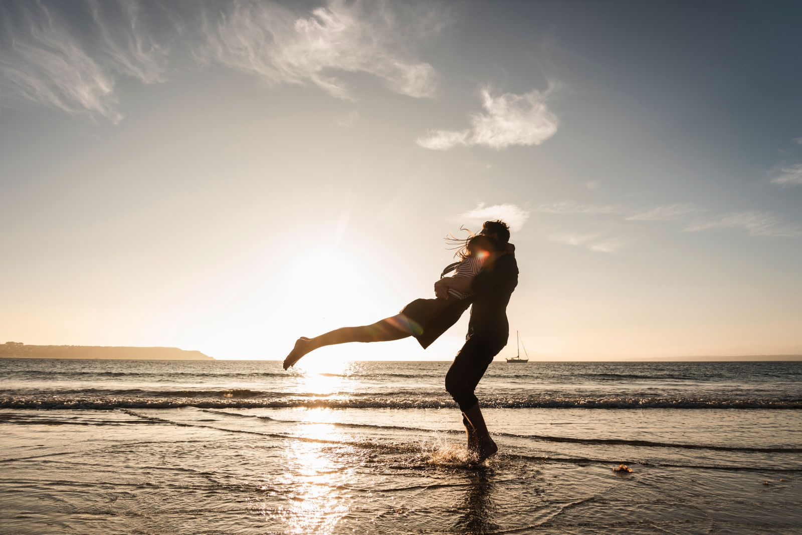 France, Brittany, happy young couple hugging on the beach at sunset