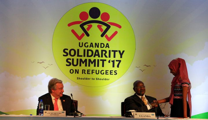 President Museveni (center), pictured here with UN Secretary General Antonio Guterres and a young refugee.