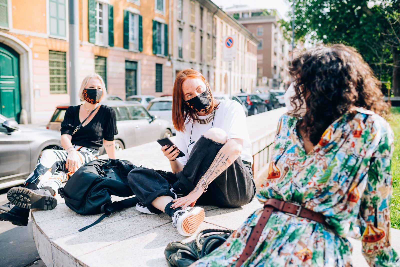 Three young women wearing face masks during Corona virus, sitting on a riverbank, chatting.