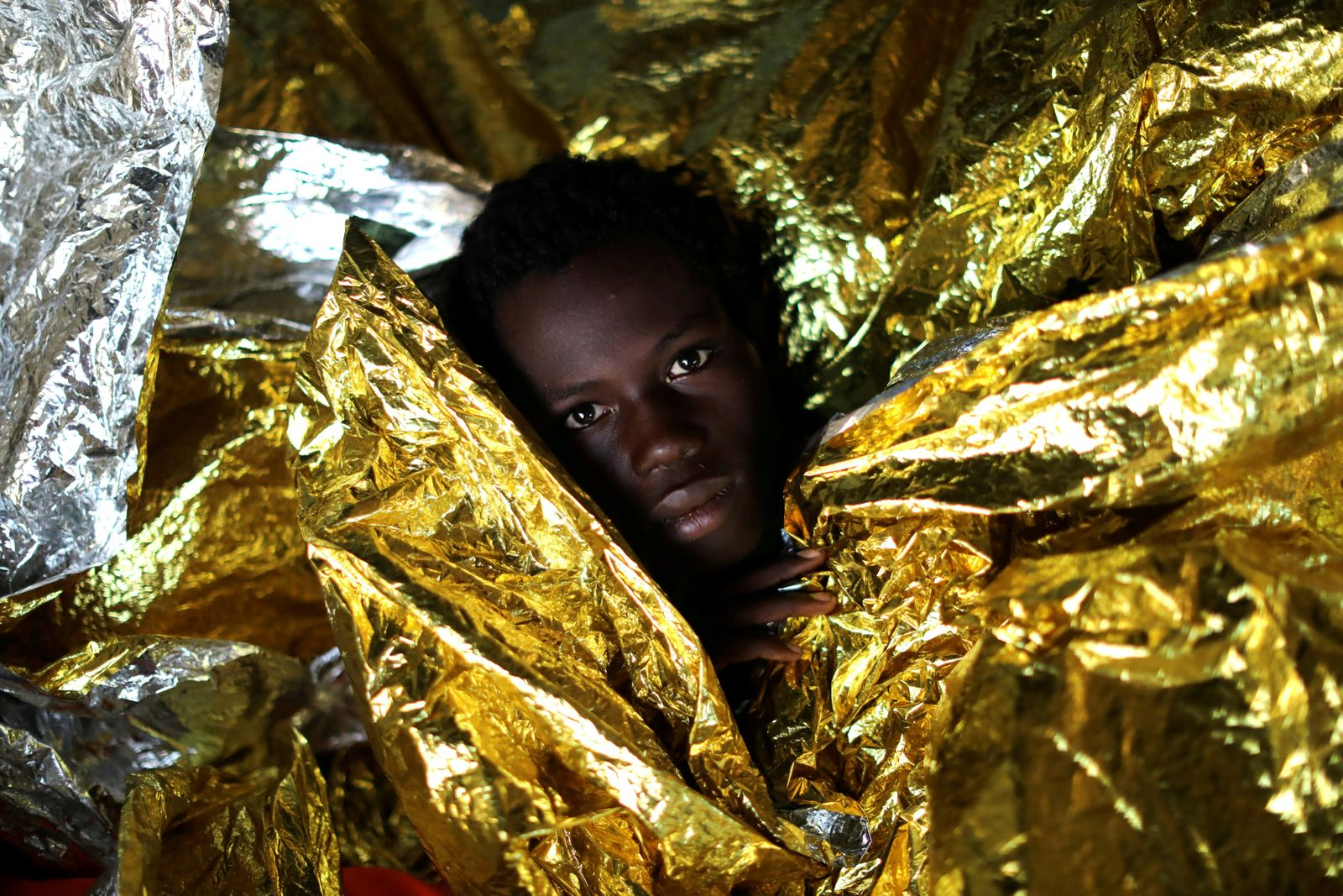 FILE PHOTO:Mamahba, 17, from Guinea is covered with thermal blankets aboard the former fishing trawler Golfo Azzurro of the Spanish NGO Proactiva Open Arms following a rescue operation near the coasts of Libya in the central Mediterranean Sea