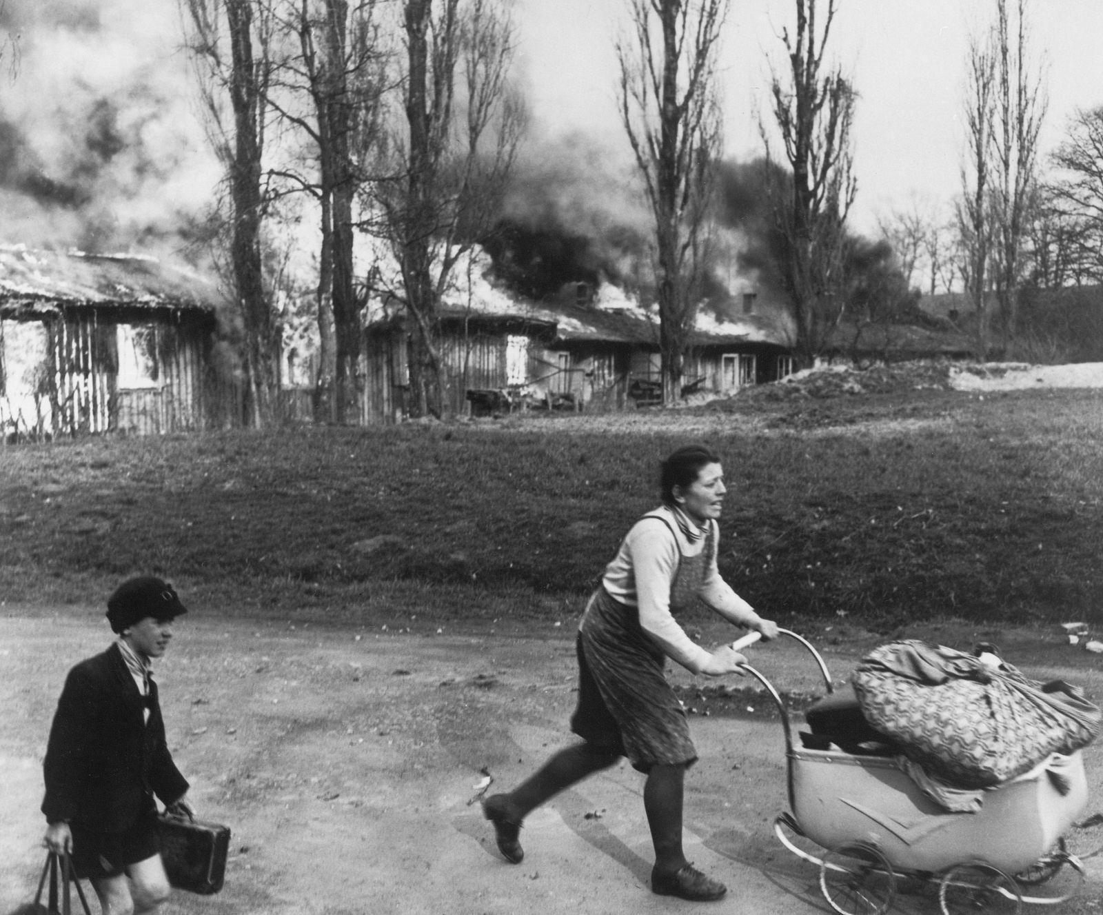 Deutsche Frauen und Kinder auf der Flucht vor brennenden Häusern