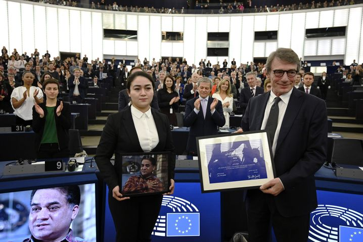 Ilham holds a portrait of her father at the European Parliament on Dec. 18, where she is seen standing next to parliamentary President David-Maria Sassoli after receiving a human rights award on her father's behalf.