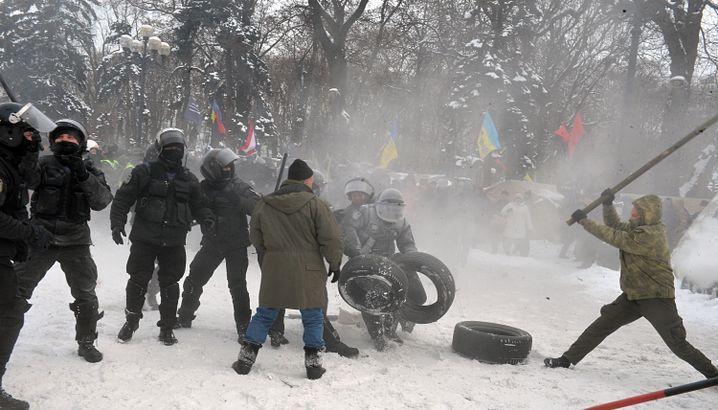 Ein Demonstrant schwingt einen Stock in Richtung eines Polizisten