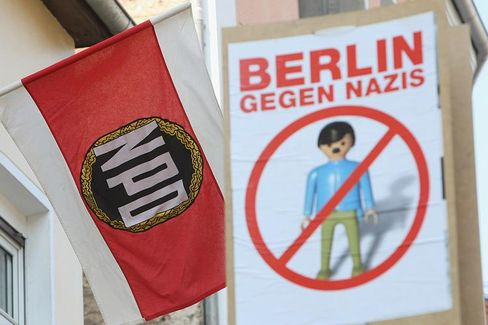 """A flag for Germany's radical right-wing party, the NPD, flies next to a protest sign saying """"Berlin against Nazis."""""""