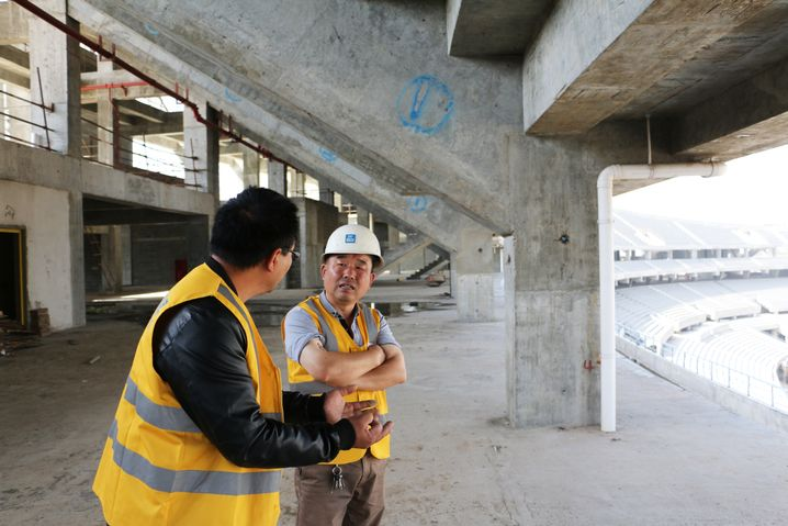 Xu Dingqiang talks to a colleague about ongoing work at the construction site.