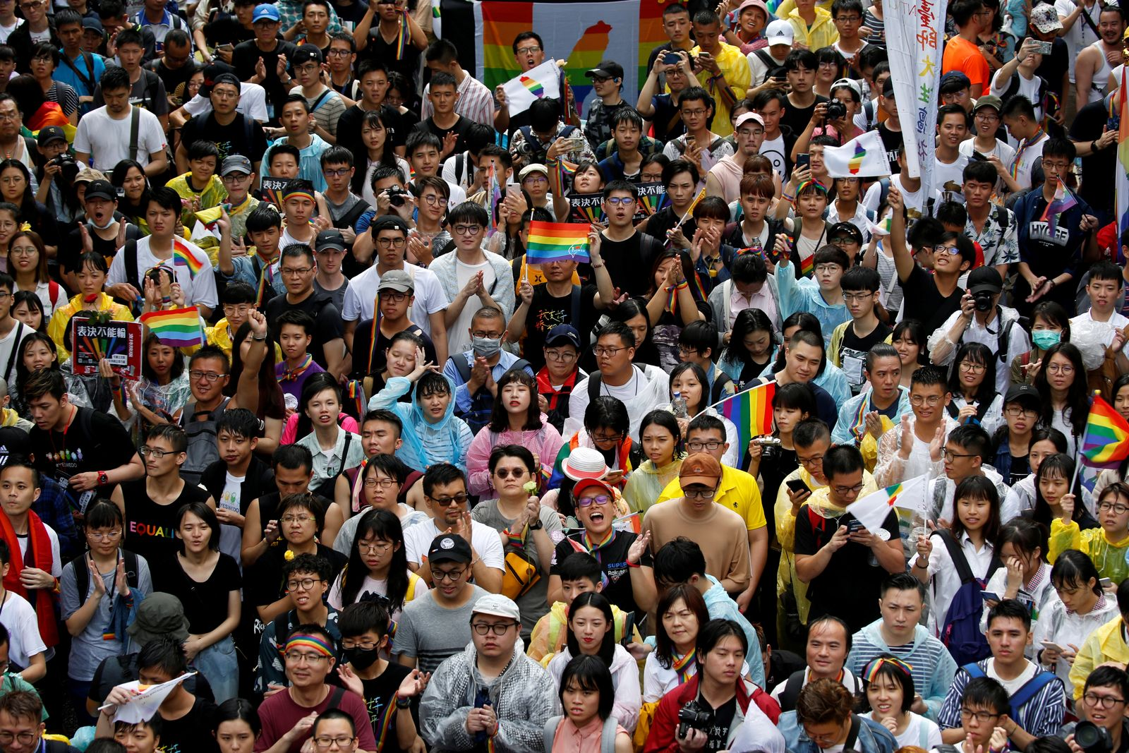 Same-sex marriage supporters hold umbrellas and rainbow flags as they take part in a rally during a parliament vote on three different draft bills of a same-sex marriage law, outside the Legislative Yuan in Taipei