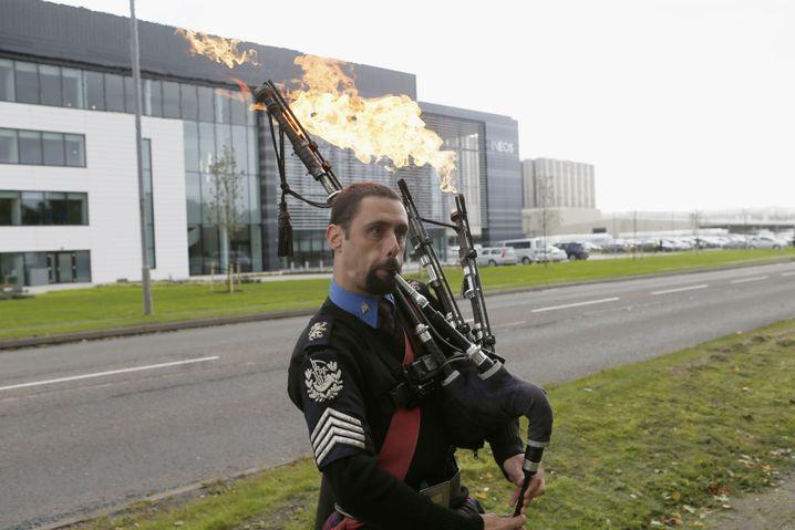 Ein Demonstrant protestiert vor dem Ineos-Sitz mit einem flammenwerfenden Dudelsack gegen die Fracking-Methoden des Unternehmens
