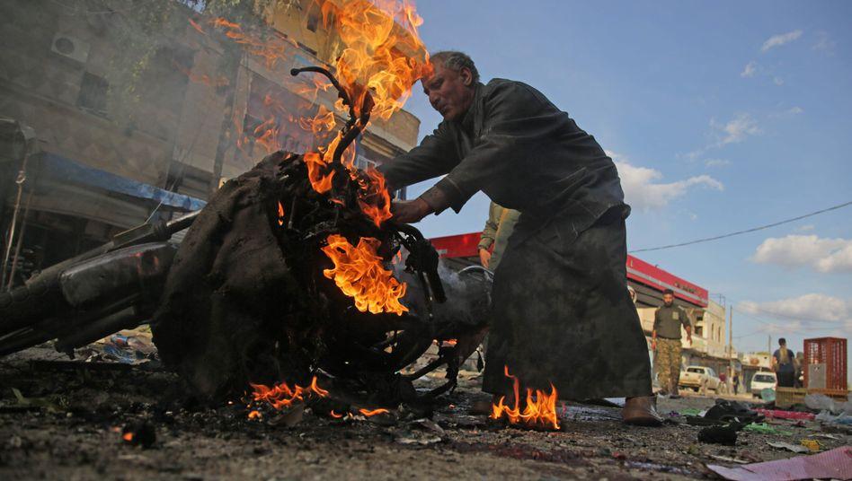 Ein Syrer birgt sein Motorrad nach der Explosion in Tall Abjad: Mindestens 15 Menschen kamen ums Leben