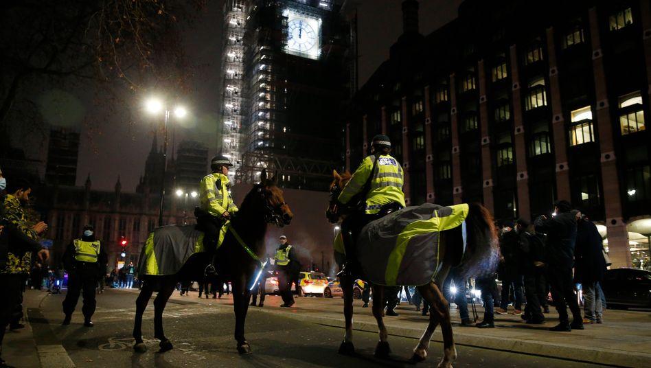 Polizisten zu Pferde vor Big Ben, wo die Brexit-Anhänger still feierten