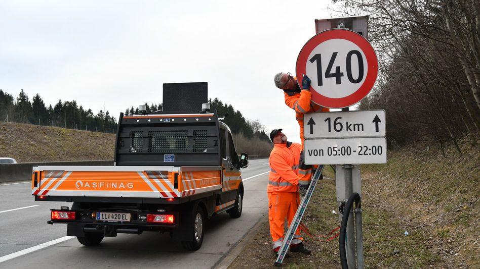 Mitarbeiter der Autobahngesellschaft Asfinag montieren ein Tempo-140-Schild auf der A1 in Oberösterreich ab