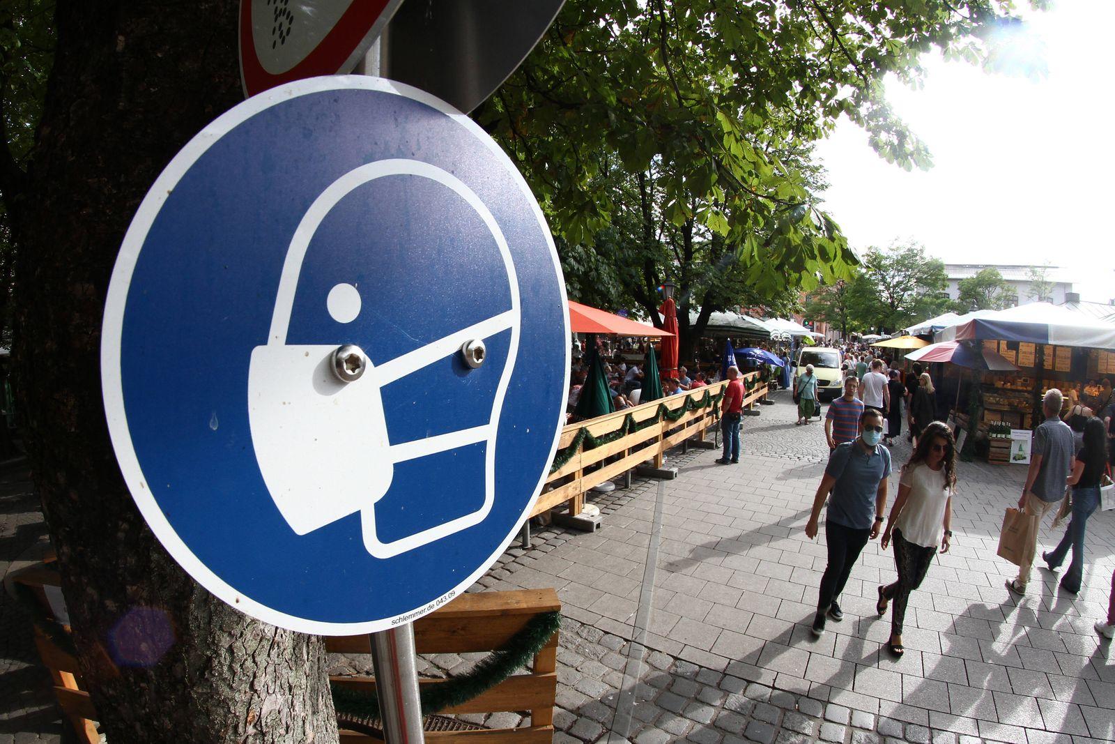 Schild mit Piktogramm Maskenpflicht am Biergarten auf dem Viktualienmarkt in der Innenstadt von M¸nchen, Bayern, Deutsch