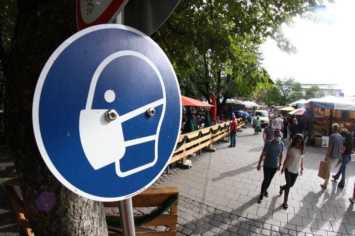 Schild zum Hinweis auf Maskenpflicht am Biergarten auf dem Münchner Viktualienmarkt