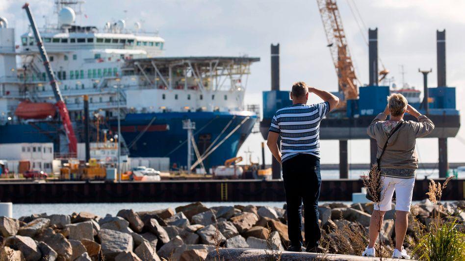 """Passanten beobachten den russischen Rohrleger """"Akademik Cherskiy"""" im Hafen von Mukran"""