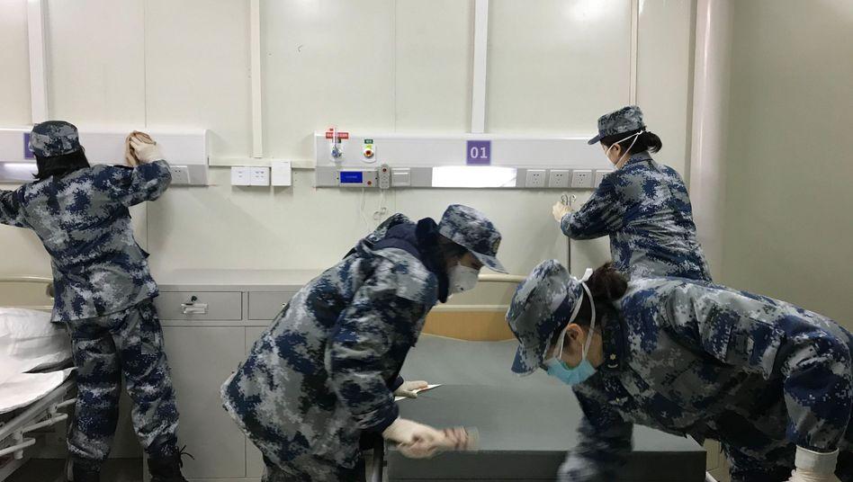 Wuhans Notkrankenhaus gegen das Coronavirus: Medizinisches Personal bereitet ein Zimmer vor