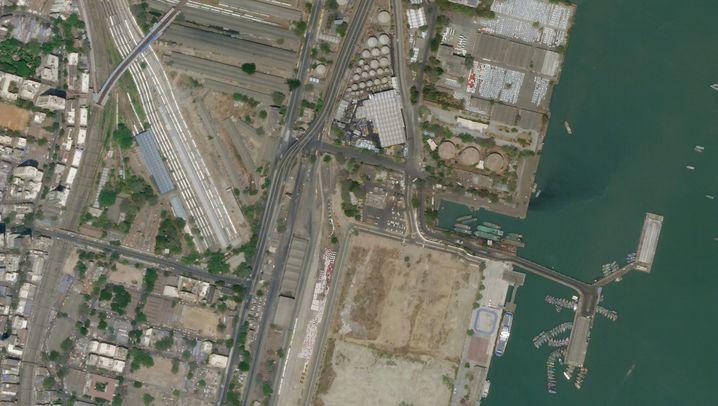 """Satellitenbild des Hafens von Mumbai """"Mumbai Port"""" (31. März 2020/13. März 2020): Schon vor seiner Gründung durch die britischen Kolonialherren 1873 wurde der natürliche Tiefwasserhafen an der Westküste Indiens für den Handel genutzt. Nach der Eröffnung des Suezkanals vier Jahre zuvor hatte sich das Import-Export-Geschäft von der Ost- an die Westküste Indiens verlagert und den Hafen von Mumbai zur wichtigsten Anlaufstelle gemacht. Ende Februar 2020 ordnete die indische Regierung für alle zwölf großen Häfen des Landes eine Überwachung und mögliche Quarantäne aller anlandenden Kreuzfahrtschiffe an, die zuvor in Ländern mit Covid-19-Infektionen gewesen waren. Kurz darauf folgten Bestimmungen für Frachtschiffe und Tanker. Inzwischen müssen die Kapitäne aller Schiffe, die einen indischen Hafen anlaufen wollen, mindestens 72 Stunden vor der Ankunft ein Dossier über die Gesundheit aller Besatzungsmitglieder an die Behörden senden."""