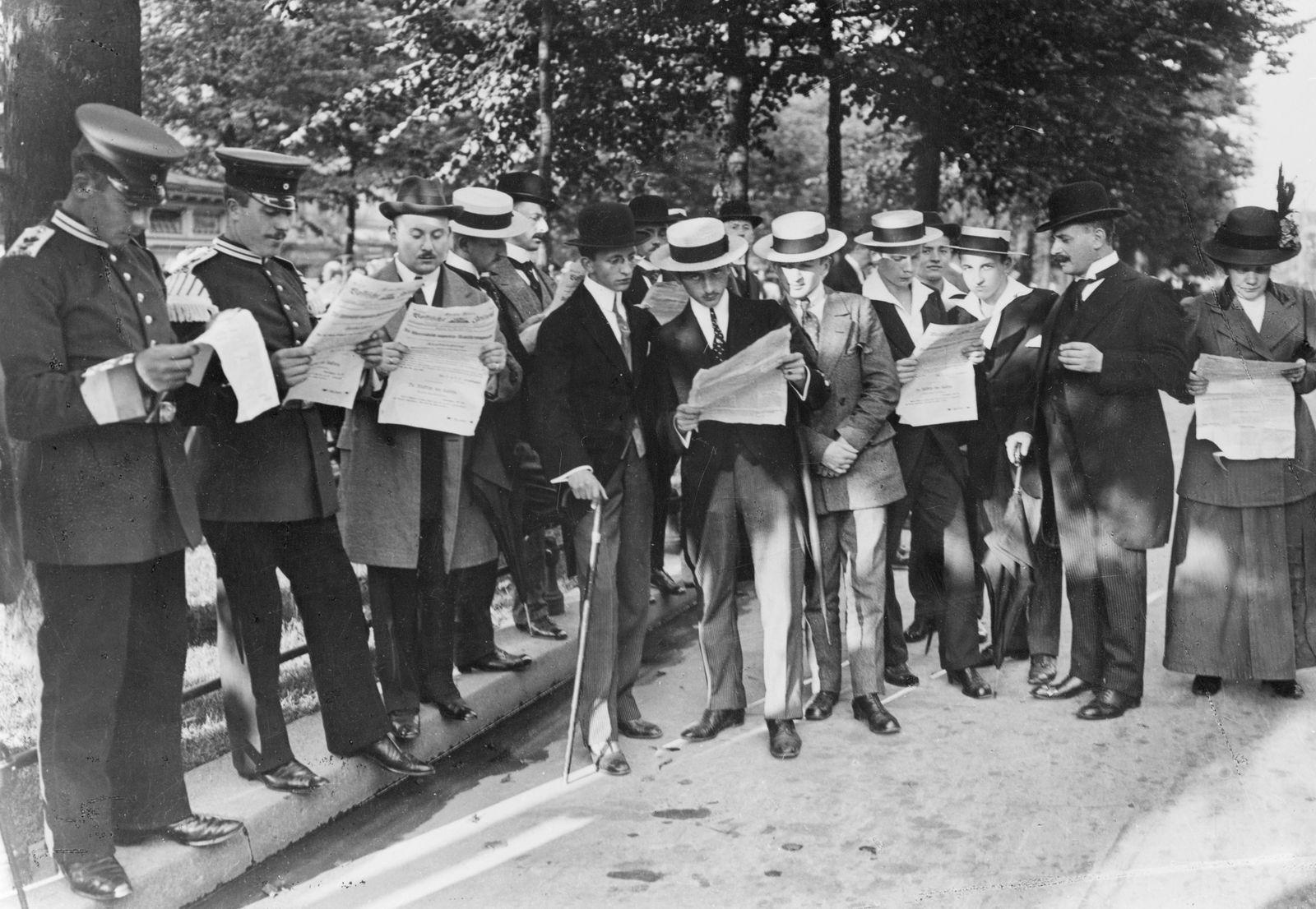 """Die Redaktion der """"Vossischen Zeitung"""" verteilt im Tiergarten Extrablätter anlässlich der Verhängung des Kriegsrechts"""