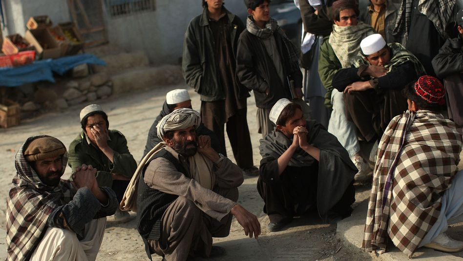 Afghan men in the village of Zerak gather for questioning by US soldiers.