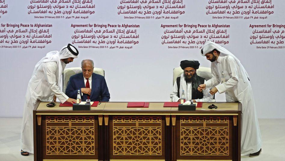 US-Diplomat Zalmay Khalilzad und Taliban-Mitgründer Abdul Ghani Baradarunterzeichnen das Friedenabkommen zwischen den USA und den Taliban in Doha