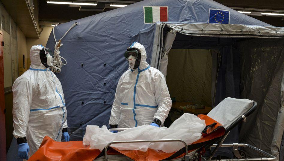 Zwei Mitarbeiter in Schutzanzügen warten in einem Krankenhaus in Turin neben einer Liege