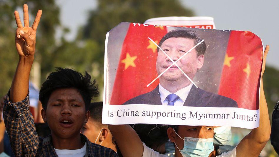 Demonstranten in Myanmar halten ein Plakat mit Kritik an China und Staatschef Xi hoch